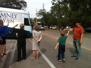 People watch and wave as Ann Romney's campaign bus pulls into the road.