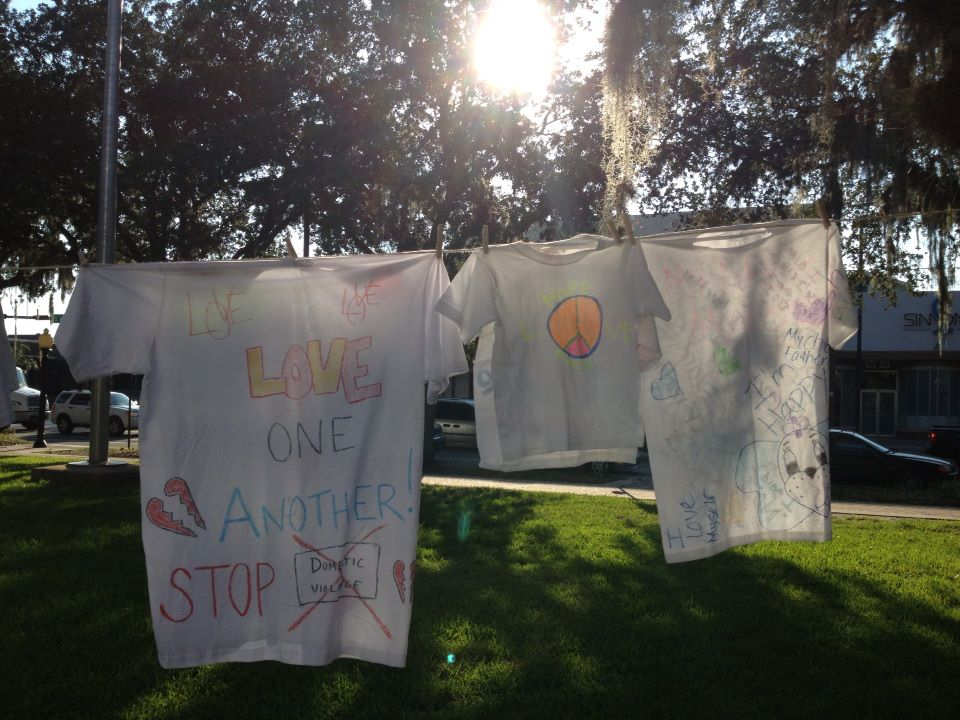 Attendees of Peaceful Paths' vigil Friday hung T-shirts in observance of Domestic Violence Awareness Month.