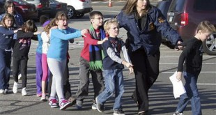 In this photo provided by the Newtown Bee, Connecticut State Police lead children from the Sandy Hook Elementary School in Newtown, Conn., following a reported shooting there Friday, Dec. 14.
