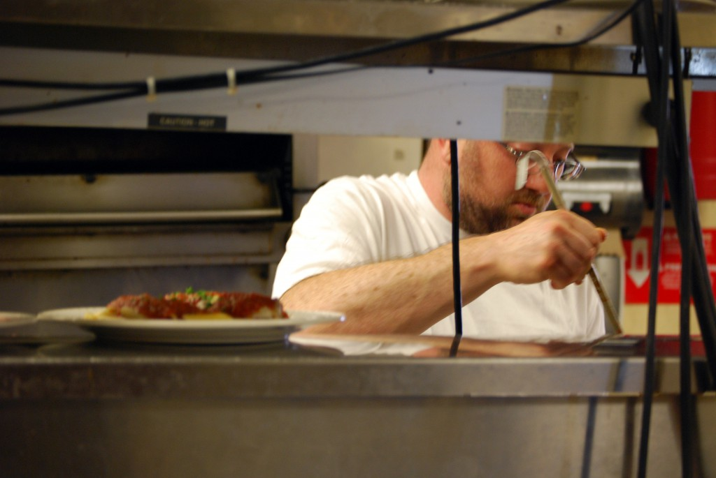 Chef Andy Fass ladles the finishing touch onto a dish soon after Amelia's Restaurant opens for lunch.