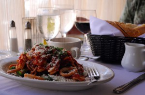 Wine, a basket of warm bread and a pasta dish with fresh grated cheese are served to a couple.