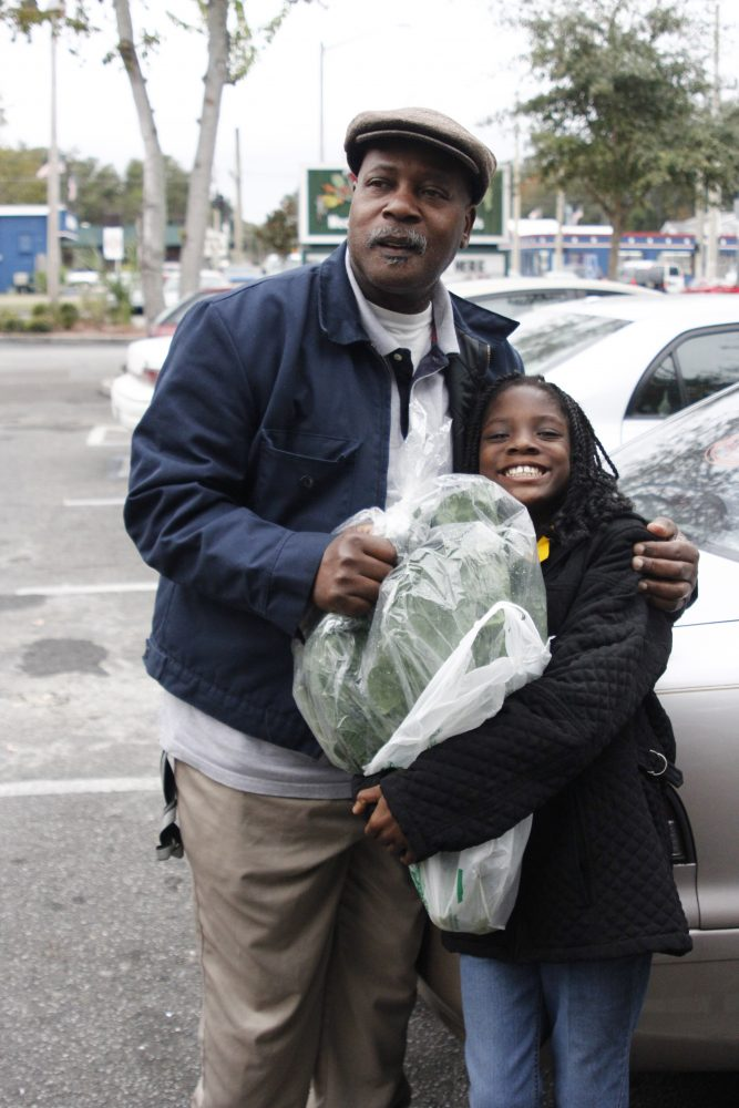 Jeremiah Gordon and his daughter packing their car with groceries outside of Ward's Supermarket.