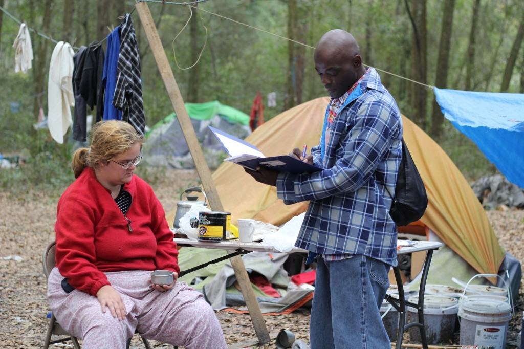 Willy Smith, volunteer, administers a survey to Victoria Morehouse in tent city located off of the Hawthorne Trail.