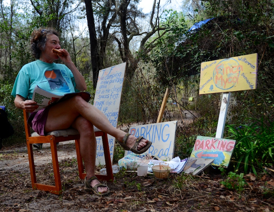 Debbie Harkrader, 56, eats a peanut butter and jelly sandwich while waiting to direct newcomers to the Florida Earthskills Gathering on Wednesday. She's a masseuse, potter and tutor from Virginia.