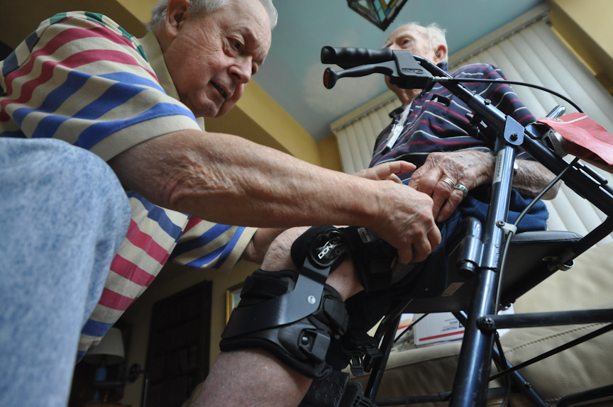 Blackwell helps Wight put on his leg brace for a walk to the pond at Oak Hammock retirement community.