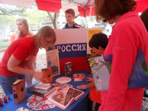 "Olesya Dudenkova, 23 (left) writes a boy's name in Russian at the 2013 ""Viva Europe!"" festival on Saturday in downtown Gainesville."