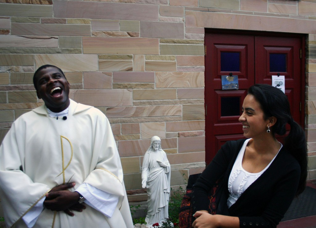 Rev. Anthony Eseke shares a joke with Maria Fernanda Pabon, 21, after mass.