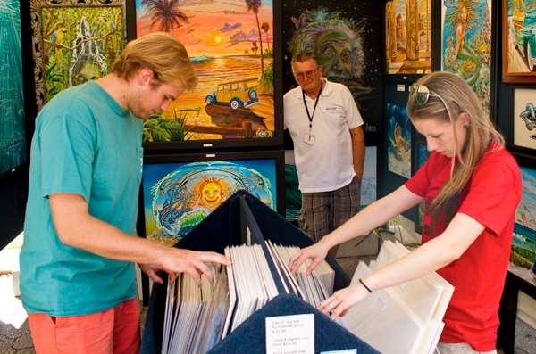 Gytis Garsys (left), a 21-year-old University of Florida student, and Kristen Brooks, 29, of Gainesville, look through the paintings of Rick Ficker (at back) on Sunday. Ficker, of Merritt Island, Fla., was one of about 200 vendors at the 44th annual Santa Fe College Spring Arts Festival in downtown Gainesville.