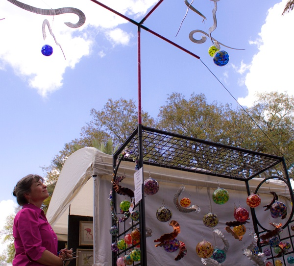 Paula Fambroso, a 54-year-old Gainesville resident, admires blown glass Sunday at the 44th annual Santa Fe College Spring Arts Festival in downtown Gainesville.