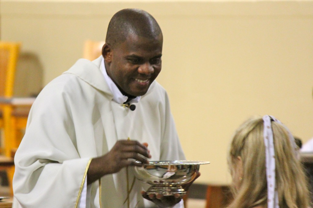 Rev. Anthony Eseke gives communion to a mass of about 150 people on April 13, 2013.