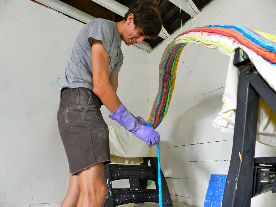 Evan Galbicka, who runs the Church of Holy Colors, dips a dyed cotton fiber strand in plaster. It will be added to other thick candy-colored strings that make up the piece, which will be displayed in F.L.A. Gallery.