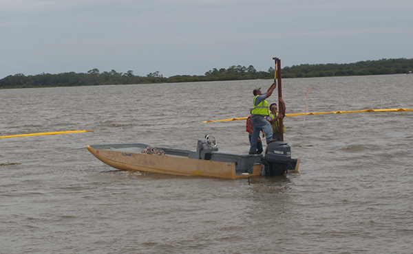 Workers in Cedar Key ensure a pole is secured to keep a barge in place.