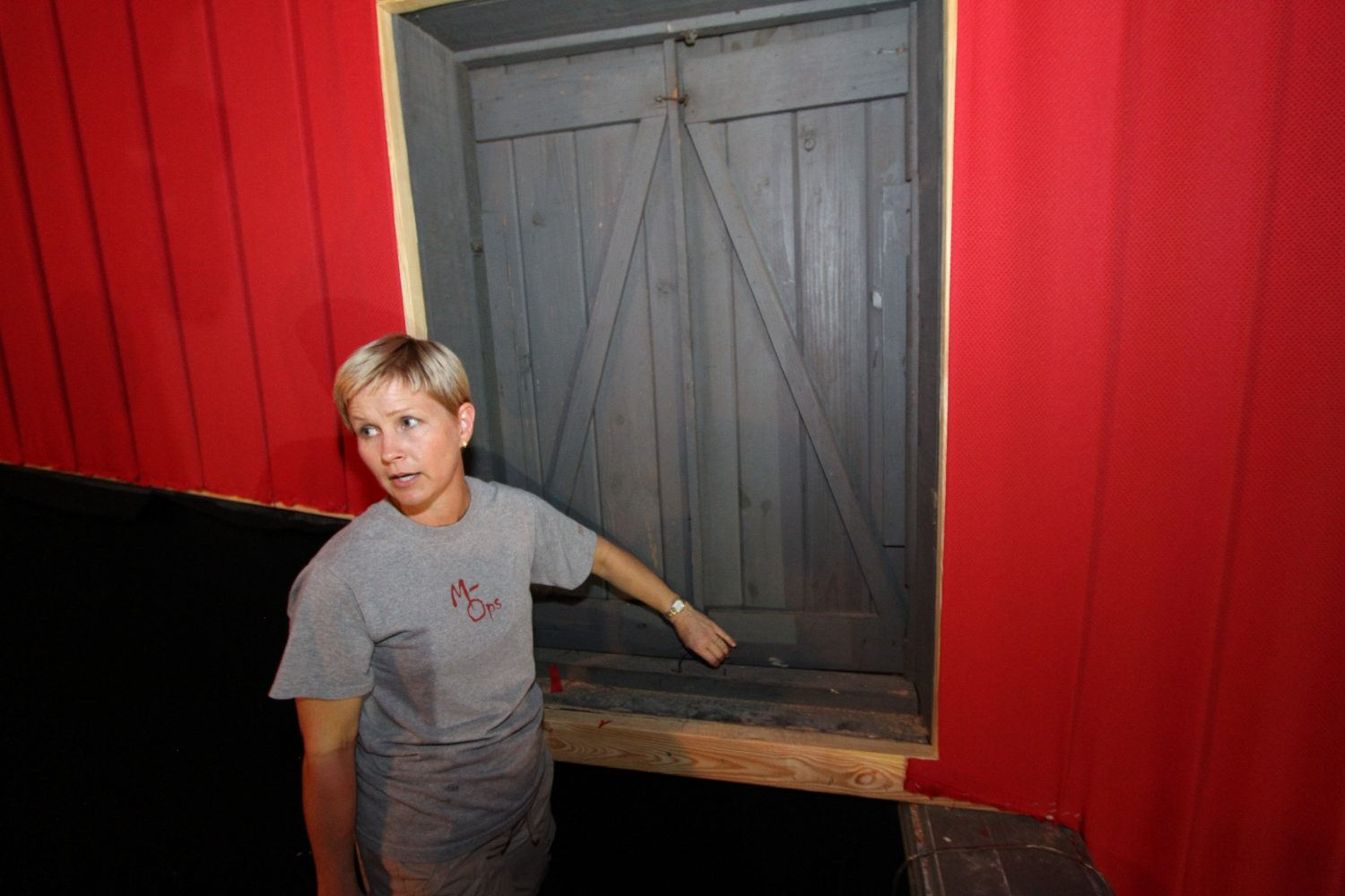 Janet Alligood stands in front of a fire escape door that is boarded shut today. In its segregated era, the door served as a fire escape for African American patrons who were forced to sit in the theatre's balcony.