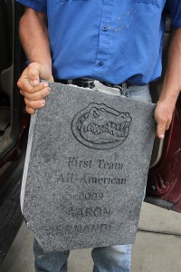 All Seasons Planning, Inc., employee Sean Skowron holds up the tile bearing Aaron Hernandez's name that was removed Thursday morning from in front of the Heavener Complex.