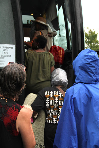 After waiting in the rain, Nancy Jones and other participants board the charter bus.