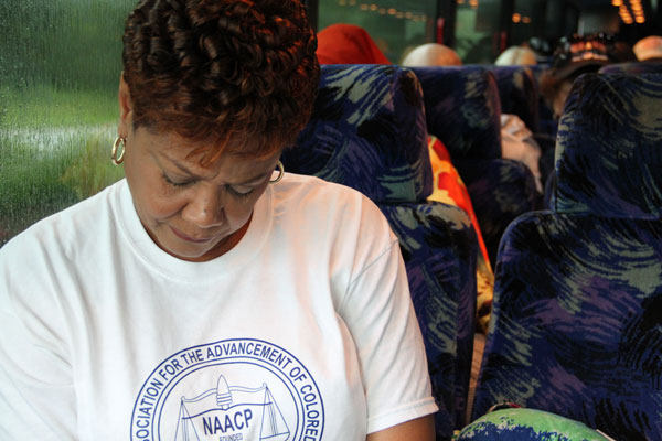 Cynthia Chestnut bows her head during a group prayer before the bus departs.