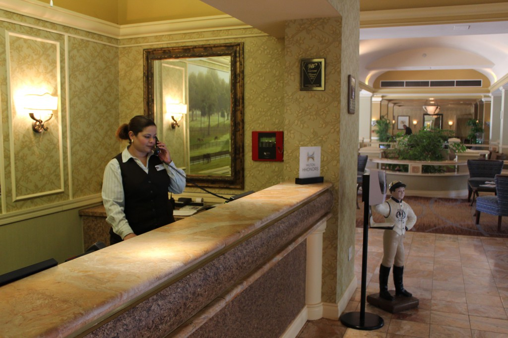 """Norma Ramos, a front desk supervisor, answers the phone for The Hilton in Ocala. Ramos said an increase in bed tax would not be welcomed in the community. """"We all need money, but no more taxes, please,"""" she said."""