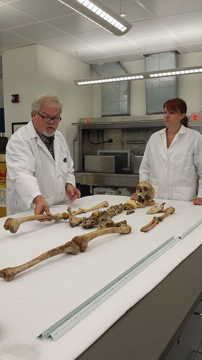 Michael Warren, program director of the C.A. Pound Human Identification Laboratory, and Michayla Schaye, a graduate analyst, examine human remains at the lab Tuesday.