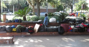 A man stands among the bags and luggage at  Bo Diddley Community Plaza Monday, an occasional meeting place for the homeless population in Gainesville.