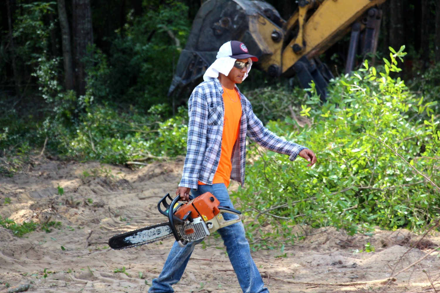 A worker cuts large limbs and works the machinery as Tioga continues to clear land. Town of Tioga has about 300 acres to build on during the next 15 to 20 years, said Greta Rice, director of sales and marketing for Tioga Realty.