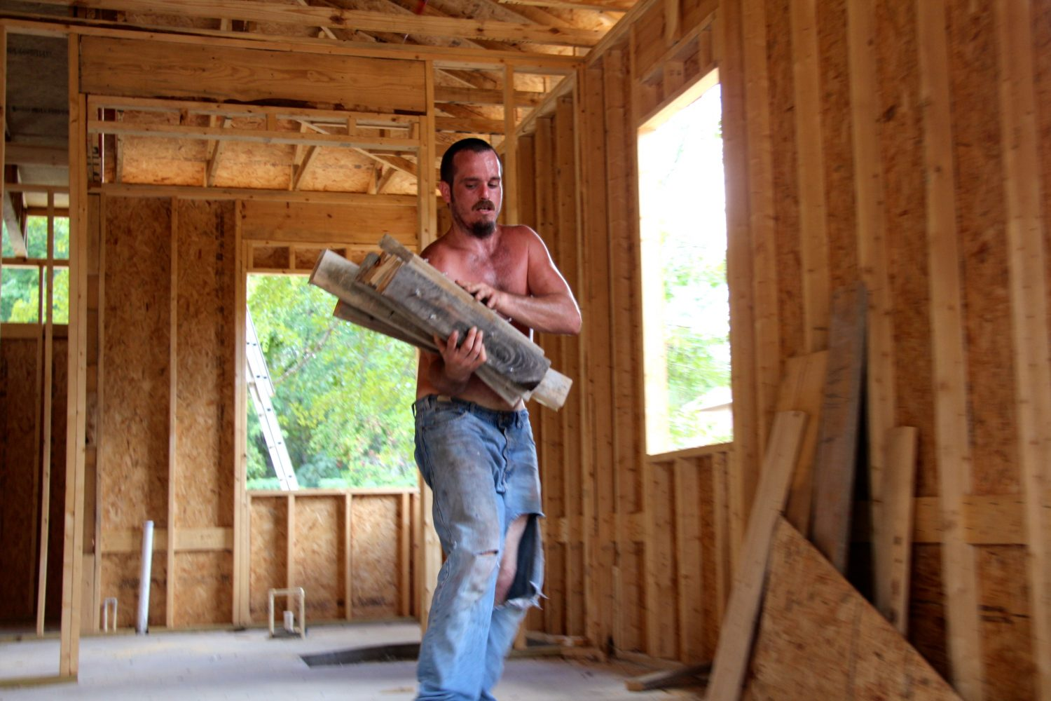 William Addison, 27, works on a house in the Gainesville heat Friday afternoon.