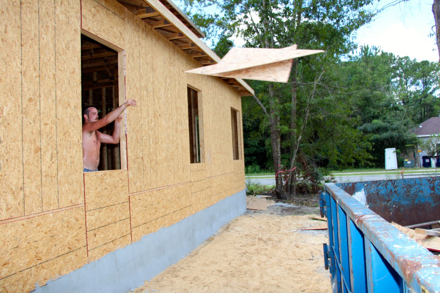 William Addison, 27, throws out excess house construction materials Friday afternoon.