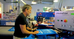 Joy Revels, owner of Dragonfly Graphics at 319 S.W. Third Ave., feeds shirts into an automatic screen-printing press during production Tuesday. The 27-year-old business produces about 2,000 shirts a week for school, business, events and churches.