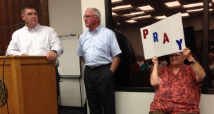 "Air quality expert Bill Straub and IWMS president Marvin Jay Barry answer questions at a town hall meeting about a biomedical waste incinerator they'd like to build in Suwannee County while Wendy Baker, 61, a retired long-time Suwannee resident, holds up a sign that says ""pray."" About 150 people came to Live Oak City Hall Thursday night to talk to the company directly"