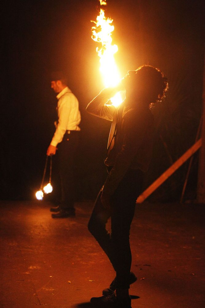 Chris Ramirez, front, and Zachary Simmons spin fire at The JAM as part of The Manic Menagerie Vaudeville Company on Saturday.