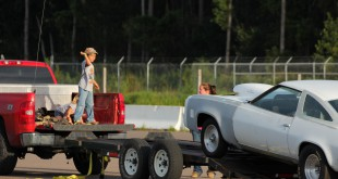 Haiden Barringer, 6, helps direct his dad in a 1973 Chevrolet Laguna off the trailer at the Gainesville Raceway last week.