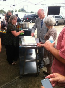 Scott cuts the birthday cake in honor of the late Dr. James Robert Cade, who would have been 86 Thursday.