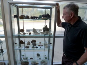 Mike Patrick, 66, examines a display case filled with sulfate minerals. Patrick obtained and arranged 24 cases of minerals, fossils and gems for an exhibit in the lobby of Building X at Santa Fe College.