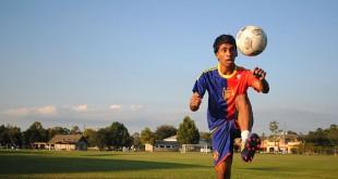 Samuel John uses his legs to juggle a soccer ball
