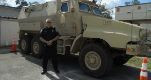 High Springs Police Chief Steve Holley stands in front of the Mine-Resistant Ambush Protected Vehicle.