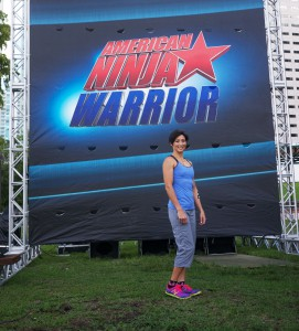 "Joyce Shahboz stands in front of a ""American Ninja Warrior"" sign at the southeast region qualifying course in Miami earlier this year. Shahboz became the only woman to make back-to-back finals in the history of the NBC show."