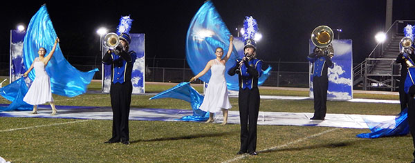 """Left to right: Courtney Evans, 17, Ian Childers, 16, Hayley Lovvorn, 15, and Kristen Hunt, 17, performing with cloud tarps and backdrops to complement the """"As Light as a Feather"""" theme."""