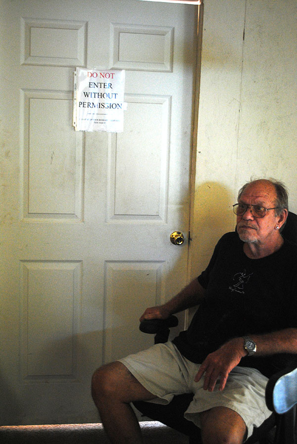 Bill Branton sits in the dining area of Samaritan Comfort, where he has lived for the last seven months. He said he was in the same spot when police officers entered the home and ripped the door behind him off the hinges to gain access to the room beyond.