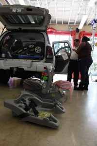 Regina Jackson, a 25-year-old mother of three, replaces her car seats with new safety devices supplied by Gainesville Fire Rescue and Safe Kids.
