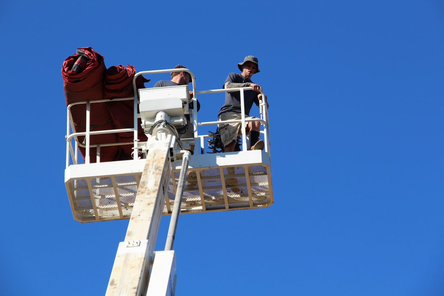 Workers take the tarps 50 feet high to place them on the rooftops of the Thomas Center.
