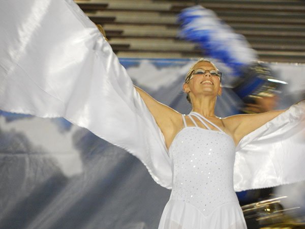 Jessica Irvine, Color Guard captain and senior at NHS, performs with a smile while incorporating movement into the flag routine.