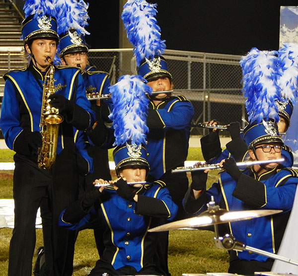 Alex Keidel, junior saxophone player (left), Meghan Olsen, junior clarinet player, Austin Demko, flute player in 8th grade, Christy Evans, senior piccolo player and Brittany Maxwell, sophomore flute player represent the woodwind sectional of the band during the show on Nov. 9.