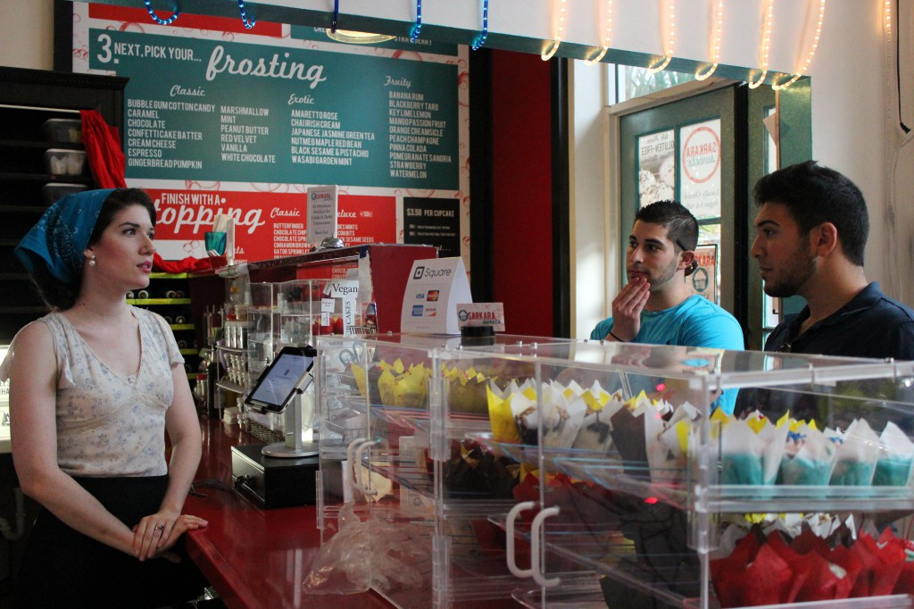 Stephanie Browning, 26, helps David Amen, 23, and Jamal Kazbour, 21, pick out cupcakes at Sarkara Sweets on Jan. 16. Sarkara Sweets recently started selling cupcakes online to cater to customers across the nation.