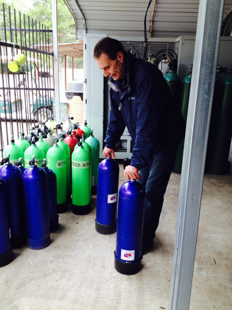 Kurt Huber, owner of Blue Grotto Dive Resort, with oxygen and nitrox tanks