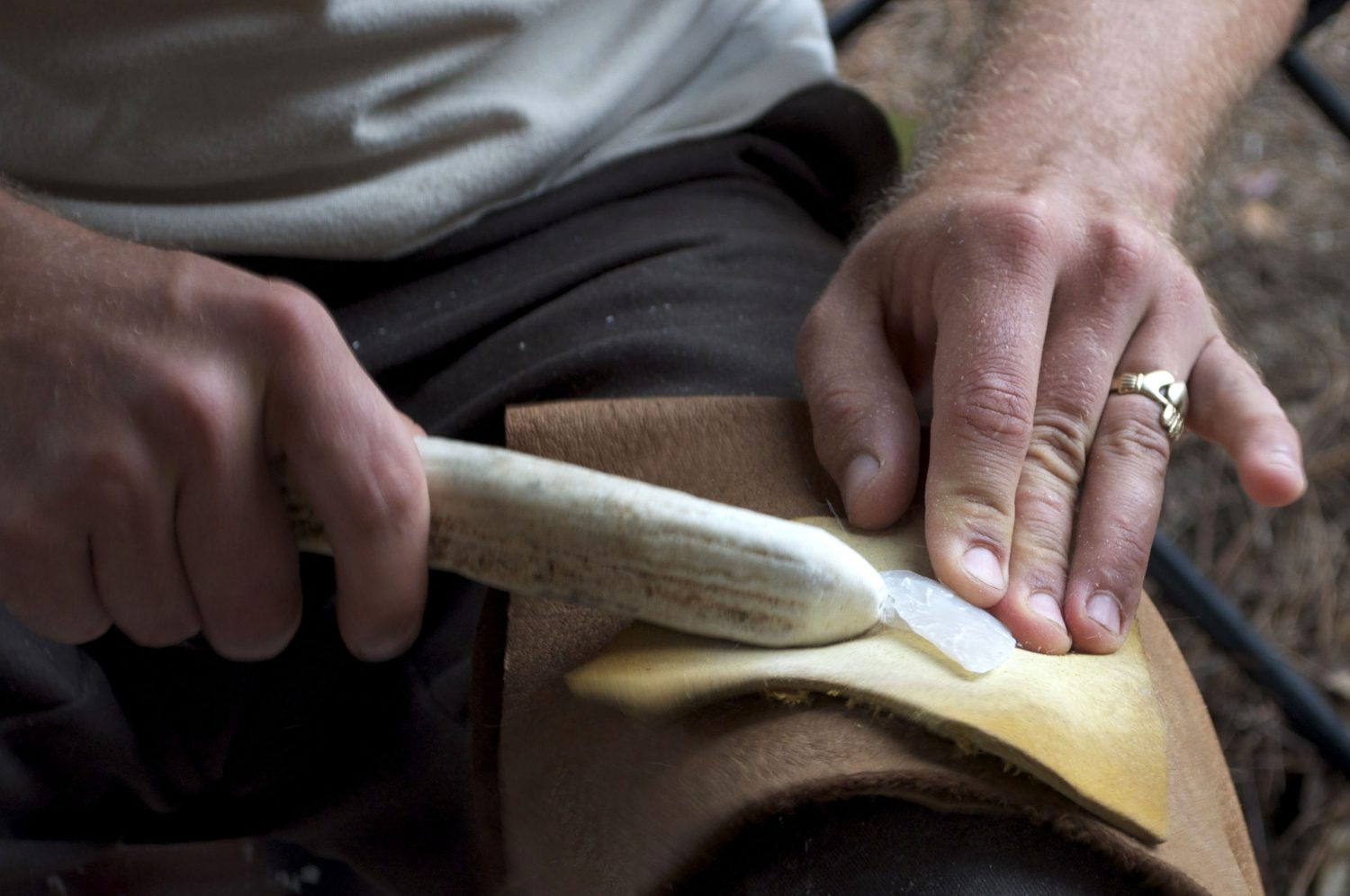 Gill protects his leg with scraps of leather while making a stone hunting point out of agatized coral. He specializes in aboriginal style flint knapping, and uses deer and elk antler tools to chip away the edges.
