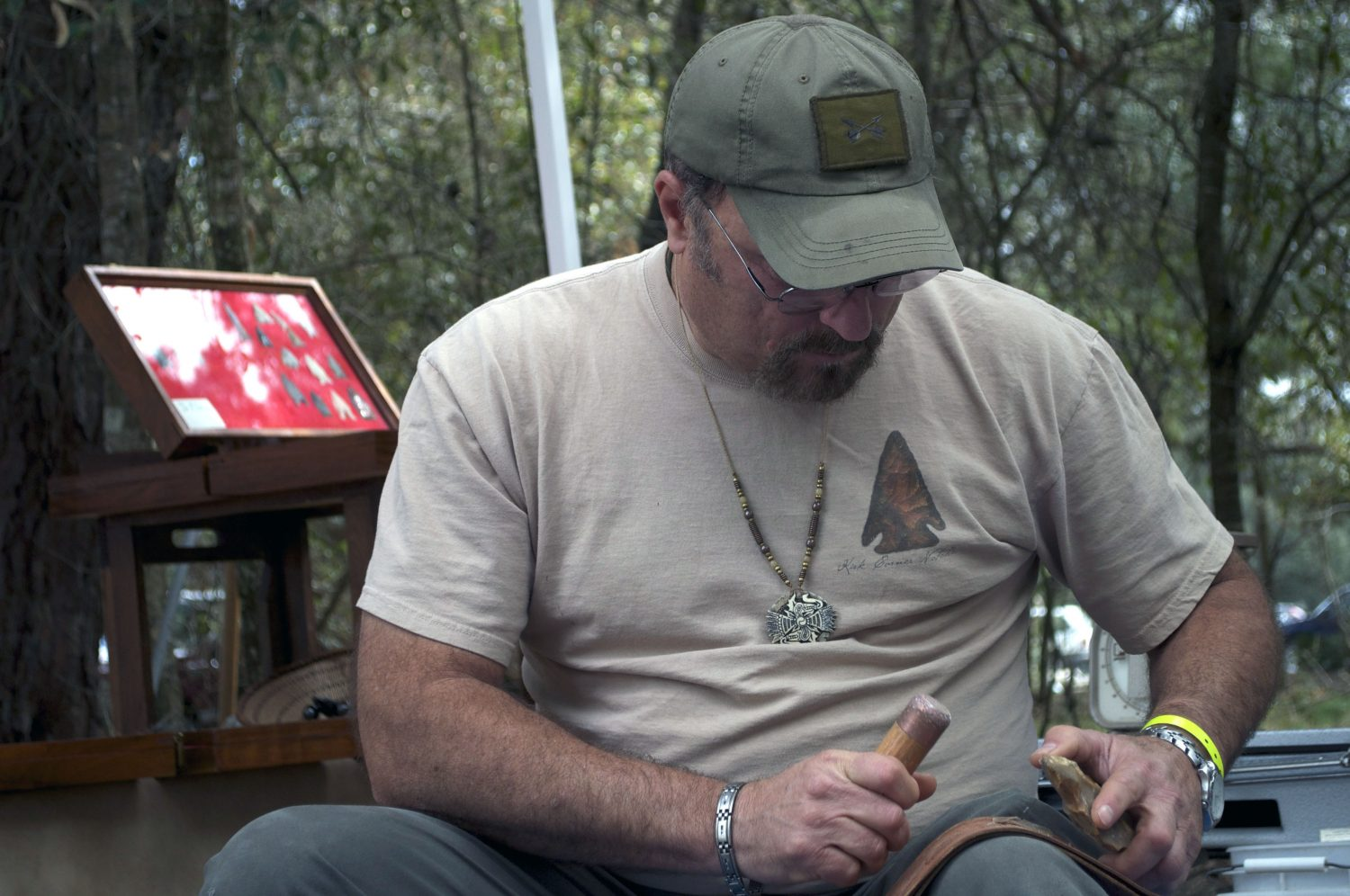 "Jeff Whitfield, a resident of Alabama, blocks out the general shape of an arrowhead at the fourth annual Silver River Knap-In in Ocala, Fla. on Saturday. ""It's all about setting up platforms to make it break where you want,"" Whitfield said."