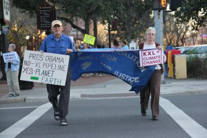 Kate Ellison of Melrose, Fla. and John Linnehan of Hampton, Fla. march across the street from Bo Diddley Plaza with protest signs on Monday night, Feb. 3rd, 2014. The pair came to Gainesville to protest the extracting and processing of tar sands, or oil sands,from Canada into useable fuel. Photo by Amber Riccinto.