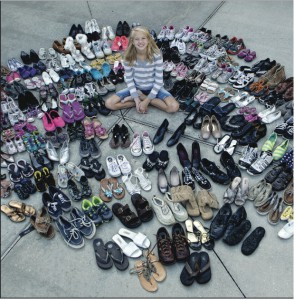 Girl surrounded by donated shoes