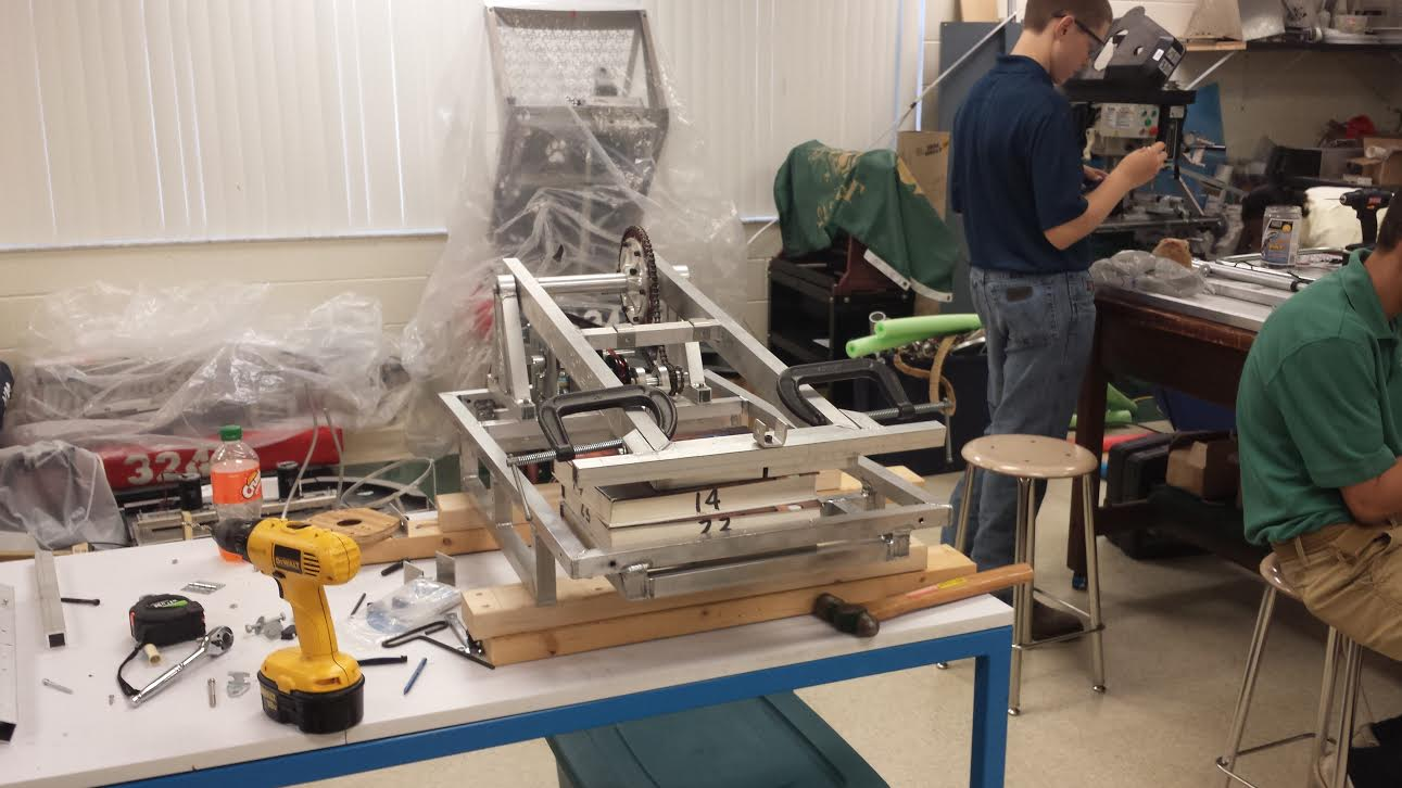 The Imagine 5 team works on finishing the robot, ensuring it can pick up and throw the 24-inch diameter ball during the upcoming competition.