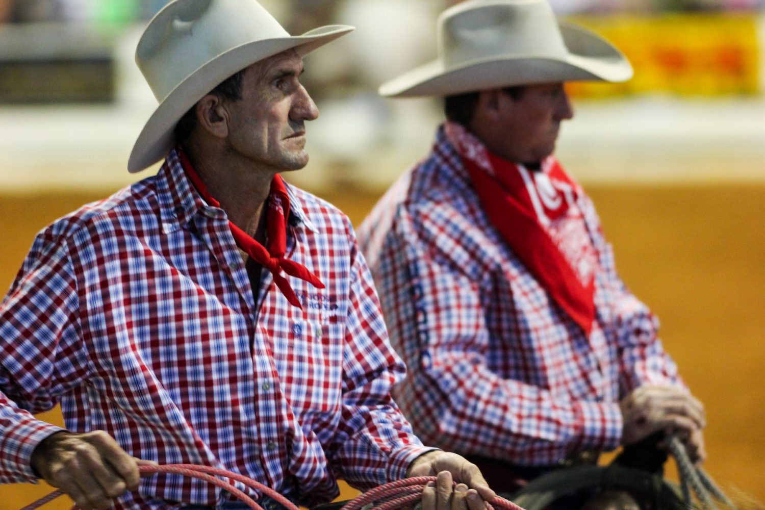 Two cowboys ride through the Southeastern Livestock Pavilion at the Ocala Pro Rodeo on Friday night, March 21, 2014.