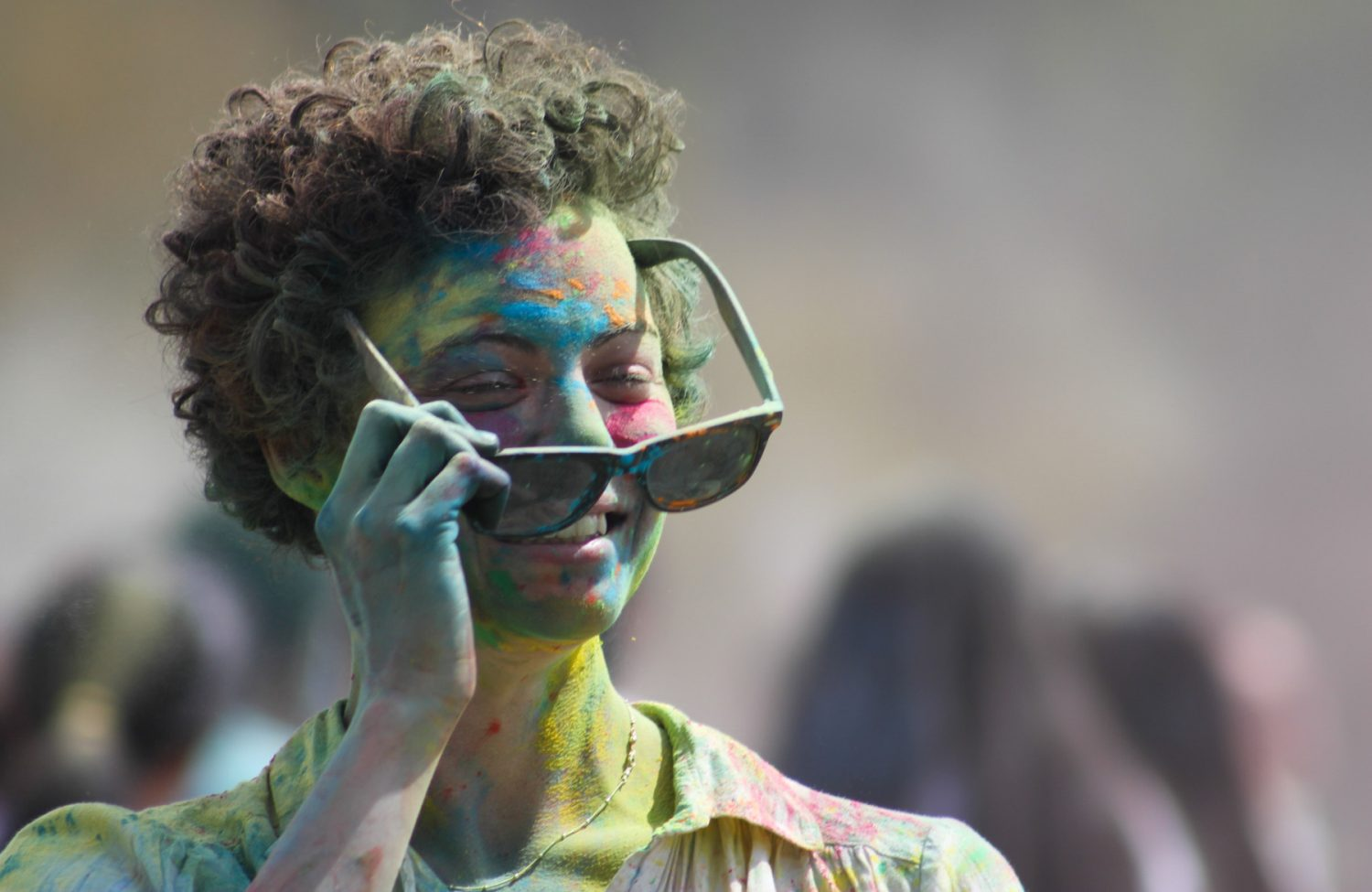 Covered in bright colors, a woman puts on her sunglasses to prevent the colored cornstarch from getting in her eyes.